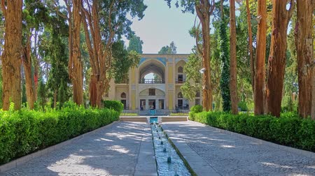isfahan : KASHAN, IRAN - OCTOBER 23, 2017: Walk along green shady alley of oldest in country Fin Garden with a view on Kushak - the scenic pool house, decorated with tiled patterns, on October 23 in Kashan. Stock Footage