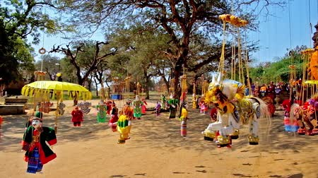 mianmar : Traditional handicraft market in Bagan - handmade toys, puppets and bright umbrellas hang on the strings from the trees around the ancient temples in archaeological site, Myanmar. Stock Footage