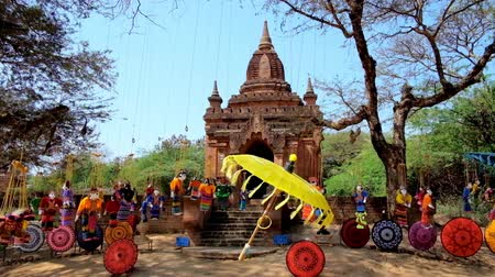 pagan kingdom : Colored handmade umbrella and beautiful string marionettes, fluttering on the wind next to the small Buddhist Shrine in archaeological site of old Bagan, Myanmar.