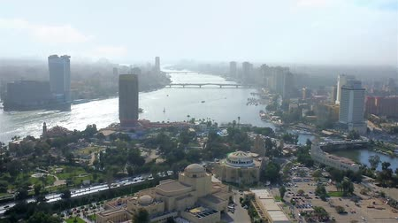 nil : Enjoy aerial cityscape of two cities from the top of Cairo Tower, overlooking Cairo, Giza, Gezira Island and curved Nile river, Egypt. Stok Video