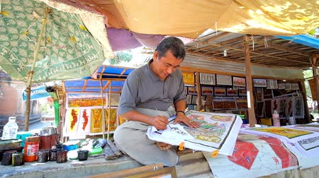 pagan kingdom : BAGAN, MYANMAR - FEBRUARY 24, 2018: The smiling artist is painting an elephant on the sheet of paper in traditional Burmese style, on February 24 in Bagan Stock Footage
