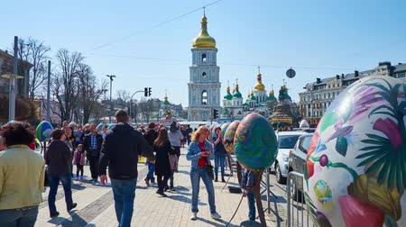 torre sineira : KIEV, UKRAINE - APRIL 14, 2018: Walk along the Easter eggs on Vladimirska street to Sofiyska square during Easter Festival, bell tower of St Sofia Cathedral rises on background, on April 14 in Kiev.