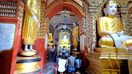 worshipers : MONYWA, MYANMAR - FEBRUARY 22, 2018: The splendid interior of  Thanboddhay Paya decorated with large golden statues of Lord Buddha and colored carvings on walls, on February 22 in Monywa. Stock Footage