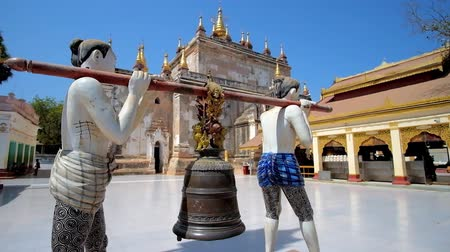 pagan kingdom : The medieval sculpture of the men, carrying big bell, that is used for Buddhist ritual of bell ringing, located in front of Manuha temple, Bagan, Myanmar. Stock Footage