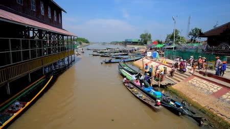 fishing village : INLE, MYANMAR - FEBRUARY 18, 2018: Hpaung Daw U Pagoda on Inle lake is popular place of pilgrimage and tourism, people arrive here on kayaks and canoes, on February 18 in Inle. Stock Footage