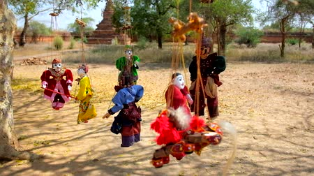 кукла : Small puppets, made of wood, cloth and papier-mache hang on the tree next to the ancient shrines of old Bagan, Myanmar. Стоковые видеозаписи
