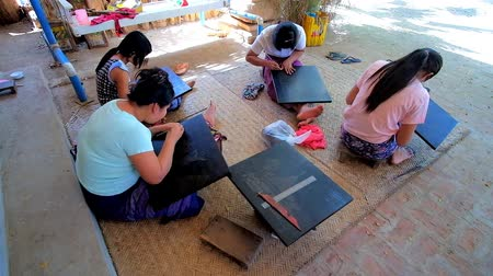 lacquerware : BAGAN, MYANMAR - FEBRUARY 24, 2018: Female artisans at work - they make images on lacquered surface, using etching needles, sitting on the floor in lacquerware workshop, on February 24 in Bagan.
