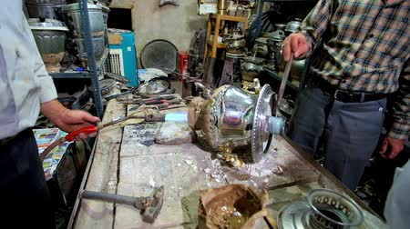 восточный базар : KASHAN, IRAN - OCTOBER 22, 2017: Master repairs and cleans up an old stainless steel samovar, using burner, hammer and other tools in small workshop, located in Grand Bazaar, on October 22 in Kashan Стоковые видеозаписи