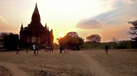 pagan kingdom : BAGAN, MYANMAR - FEBRUARY 26, 2018: Group of teens play chinlone (caneball) - traditional Burmese sport, amid the ancient temples of Old Bagan archaeological site on sunset, on February 26 in Bagan