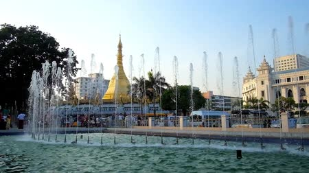 paya : YANGON, MYANMAR - FEBRUARY 15, 2018: The view on golden Sule Pagoda through the fountains of Maha Bandula Garden, located in Downtown, on February 15 in Yangon.