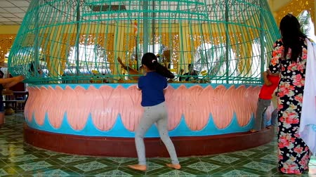 mianmar : BAGO, MYANMAR - FEBRUARY 15, 2018: Kids throw coins to pavilion for donations with spinning installation in Shwemawdaw Pagoda, on February 15 in Bago.
