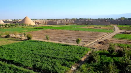 historical : Panorama of farm lands, surrounded by medieval adobe rampart of Ghaleh Jalali citadel with a view on preserved yakhchals - ancient evaporative coolers, shaped as pyramids, Kashan, Iran.