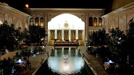 caravanserai : KASHAN, IRAN - OCTOBER 23, 2017: The courtyard of Mahin Saraye Raheb historical house - hotel with mirror pond, small garden, outdor restaurant and interesting architecture, on October 23 in Kashan. Stock Footage