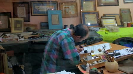 isfahan : KASHAN, IRAN - OCTOBER 23, 2017: Calligrapher rewrites the surahs of Quran, sitting in his workshop with many examples of his work - Persian and Arabic inscriptions in frames, on October 23 in Kashan.