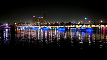 nil : CAIRO, EGYPT - DECEMBER 23, 2017: Illumination of Qasr El Nil bridge is reflected in black waters of Nile river, Cairo Tower and buildings of Gezira Island are seen behind it, on December 23 in Cairo.