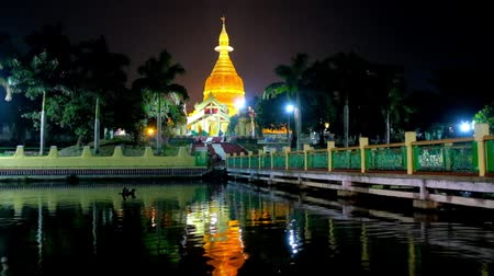 paya : The evening walk at the ponds of Mahavijaya Pagoda with  view on garden, golden stupa and its reflection in black waters, Yangon, Myanmar.
