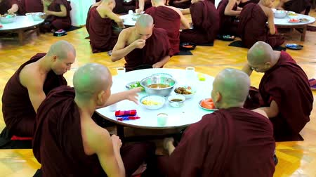 mianmar : BAGO, MYANMAR - FEBRUARY 15, 2018: The bhikkhu monks sit on the floor at the table in dining hall of Kha Khat Waing Kyaung Monastery and have the lunch, on February 15 in Bago. Stock Footage