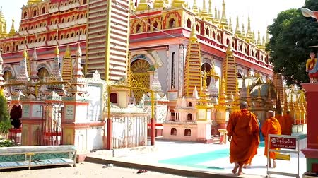 worshipers : MONYWA, MYANMAR - FEBRUARY 22, 2018: The group of bhikkhu monks goes to  Thanboddhay Paya decorated with colorful relief patterns, small stupas and numerous golden details, on February 22 in Monywa. Stock Footage