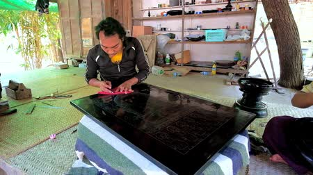 lacquerware : BAGAN, MYANMAR - FEBRUARY 25, 2018: The artisan creates the picture on lacquer panel, scratching it with etching needle, sitting in pavilion of lacquerware workshop, on February 25 in Bagan.