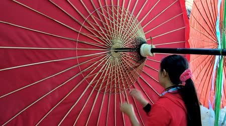 pagan kingdom : BAGAN, MYANMAR - FEBRUARY 25, 2018: The young worker makes large traditional umbrella in handicraft workshop, she fixes bamboo ribs with thread and spins umbrella, on February 25 in Bagan.