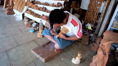 soška : BAGAN, MYANMAR - FEBRUARY 25, 2018: The carving master creates the sculpture next to his stall, located in Shwezigon Pagoda market, on February 25 in Bagan. Dostupné videozáznamy