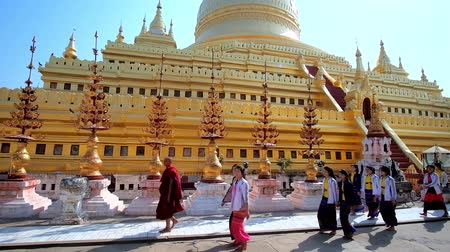 nyaung u : BAGAN, MYANMAR - FEBRUARY 25, 2018: Tourists and Buddhist pilgrims walk along the main stupa of Shwezigon Pagoda, decorated with carved spires with golden flowers and bells, on February 25 in Bagan