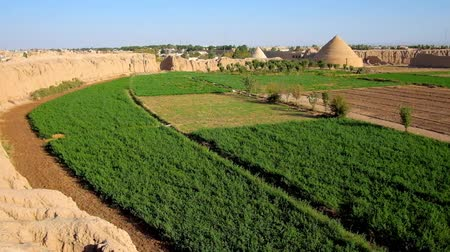 esfahan : The ruins of adobe Ghaleh Jalali citadel with agricultural lands inside of ramparts and yakhchal pyramids - ancient evaporative coolers on background, Kashan, Iran.
