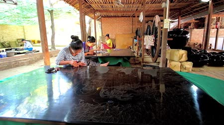 lacquerware : BAGAN, MYANMAR - FEBRUARY 25, 2018: Authentic lacquerware workshop with numerous workers, creating pictures, tableware and souvenirs in unique technique, popular in region, on February 25 in Bagan.
