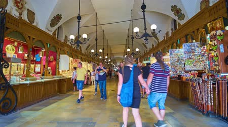 sukiennice : KRAKOW, POLAND - JUNE 10, 2018: Crowded medieval gallery of Cloth Hall (Sukiennice) with handicraft stalls, located in Main Square (Plac Mariacki) of the Old Town (Stare Miasto), on June 10 in Krakow.