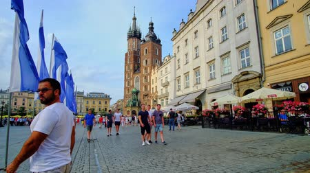 sukiennice : KRAKOW, POLAND - JUNE 10, 2018: People walk in Main Square (Plac Mariacki) of Old Town (Stare Miasto) with a view on restaurants, medieval mansions and Gothic St Mary Basilica, on June 10 in Krakow.