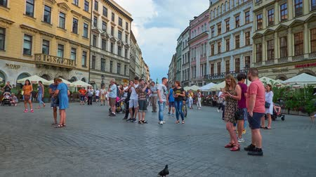 sukiennice : KRAKOW, POLAND - JUNE 10, 2018: The cityscape with historical townhouses, cozy outdoor cafes, tourist stores and places of interest in Grodzka street and Main Square of Old Town, on June 10 in Krakow.