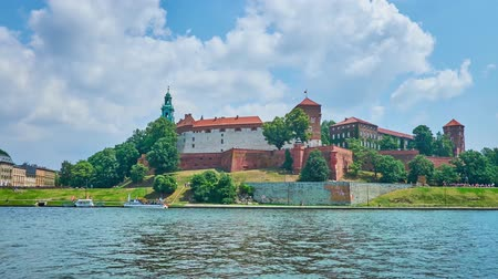 wawel : Fast running clouds over the medieval Wawel Fortress, topping the green hill in Krakow with a view on wide Vistula river on the foreground, Poland.