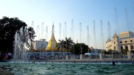 barma : YANGON, MYANMAR - FEBRUARY 15, 2018: The Maha Bandula Garden in Downtown boasts beautiful refreshing fountains, opening the view on golden Sule Pagoda, on February 15 in Yangon.