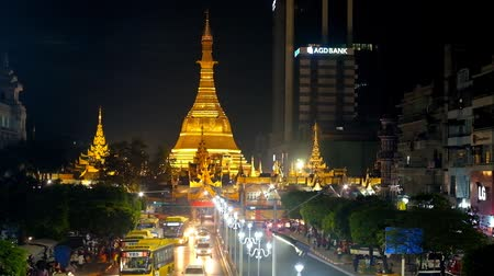 Çin mahallesi : YANGON, MYANMAR - FEBRUARY 15, 2018: The huge golden stupa of medieval Sule Paya rises over the dark evening street of the city, on February 15 in Yangon.