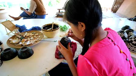mianmar : BAGAN, MYANMAR - FEBRUARY 25, 2018: The young artisan demonstrates the art of eggshell inlay, decorating the small lacquer tea bowl in traditional lacquerware workshop, on February 25 in Bagan Stock Footage
