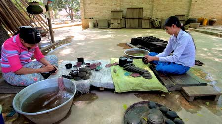 lacquerware : BAGAN, MYANMAR - FEBRUARY 25, 2018: The workers of lacquerware workshop polish the lacquer bowls, on February 25 in Bagan