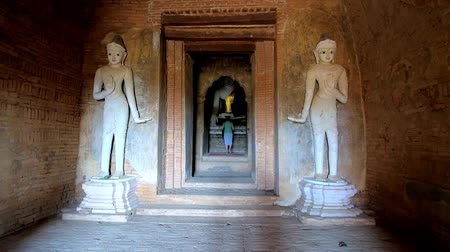 pagan kingdom : BAGAN, MYANMAR - FEBRUARY 25, 2018: Interior of ancient temple in archaeological site of Old Bagan, giant guard statues located at entrance to image house with Sitting Buddha, on February 25 in Bagan.