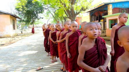 pagan kingdom : BAGAN, MYANMAR - FEBRUARY 25, 2018: The little novice bhikkhu monks of Shwe Gu Buddhist Training Monastery stand in queue for orphan donations, on February 25 in Bagan.