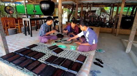 mianmar : BAGAN, MYANMAR - FEBRUARY 25, 2018: The young workers of lacquerware workshop cover small wooden planks with lacquer, on February 25 in Bagan. Stock Footage