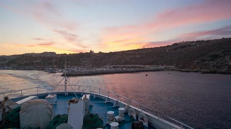 Мальта : GHAJNSIELEM, MALTA - JUNE 15, 2018: The ferry trip from Gozo to Malta island with a view on harbor, town on the hills and silhouettes of churches and fortress on sunset, on June 15 in Ghajnsielem.