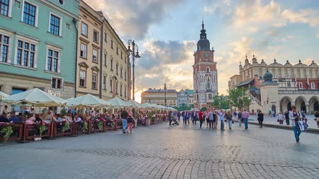 kamienice : KRAKOW, POLAND - JUNE 21, 2018: The Main Market Square with medieval townhouses, Town Hall Tower, Cloth Hall, old restaurants, cozy cafes and beer bars, on June 21 in Krakow. Stock Footage