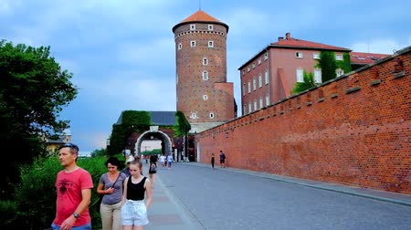 wawel : KRAKOW, POLAND - JUNE 10, 2018: The walk along the Castle Road to the gate of Wawel Castle with a view on brick rampart and Sandomierska Tower, on June 10 in Krakow. Stock Footage