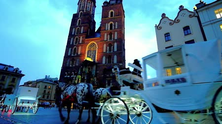 kamienice : KRAKOW, POLAND - JUNE 10, 2018: The carriage ride is popular and romantic tourist attraction in city, starting from the Market Square, next to St Mary Basilica, on June 10 in Krakow.