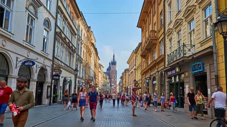 kamienice : KRAKOW, POLAND - JUNE 12, 2018: Lazy walk along the crowded Florianska street with stores, cafes and bars to the Main Square with a view on Gothic bell towers of St Mary Church, on June 12 in Krakow.