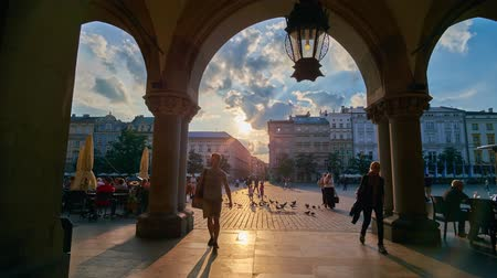 kamienice : KRAKOW, POLAND - JUNE 12, 2018: Arcade of Cloth Hall (Sukiennice) opens the view on crowded Main Square with sunset sky, historic townhouses, cozy cafes and flock of pigeons, on June 12 in Krakow. Stock Footage
