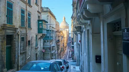 john : VALLETTA, MALTA - JUNE 17, 2018: The walk along the narrow Old Mint street with descents and climbs with a view on giant dome of Carmelite Church and historical mansions, on June 17 in Valletta.