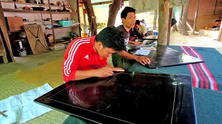 lacquerware : BAGAN, MYANMAR - FEBRUARY 25, 2018: The young artisan makes the pictures on lacquer panels, using etching needles and other tools in traditional lacquerware workshop, on February 25 in Bagan. Stock Footage