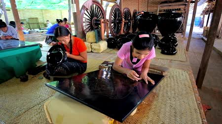 lacquerware : BAGAN, MYANMAR - FEBRUARY 25, 2018: The teen artisans of lacquerware workshop work with tableware and lacquer panels, making traditional Burmese patterns and images, on February 25 in Bagan. Stock Footage