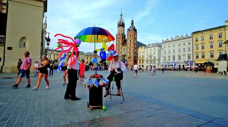 kamienice : KRAKOW, POLAND - JUNE 10, 2018: The vendors make colorful figures of animals, attracting little customers to visit air balloon stall on Main Market Square, on June 10 in Krakow. Stock Footage