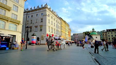 kamienice : KRAKOW, POLAND - JUNE 10, 2018: The Mariacki Square is the notable landmark of Old Town with historical churches, scenic mansions, riding old-fashioned carriages and cozy cafes, on June 10 in Krakow.